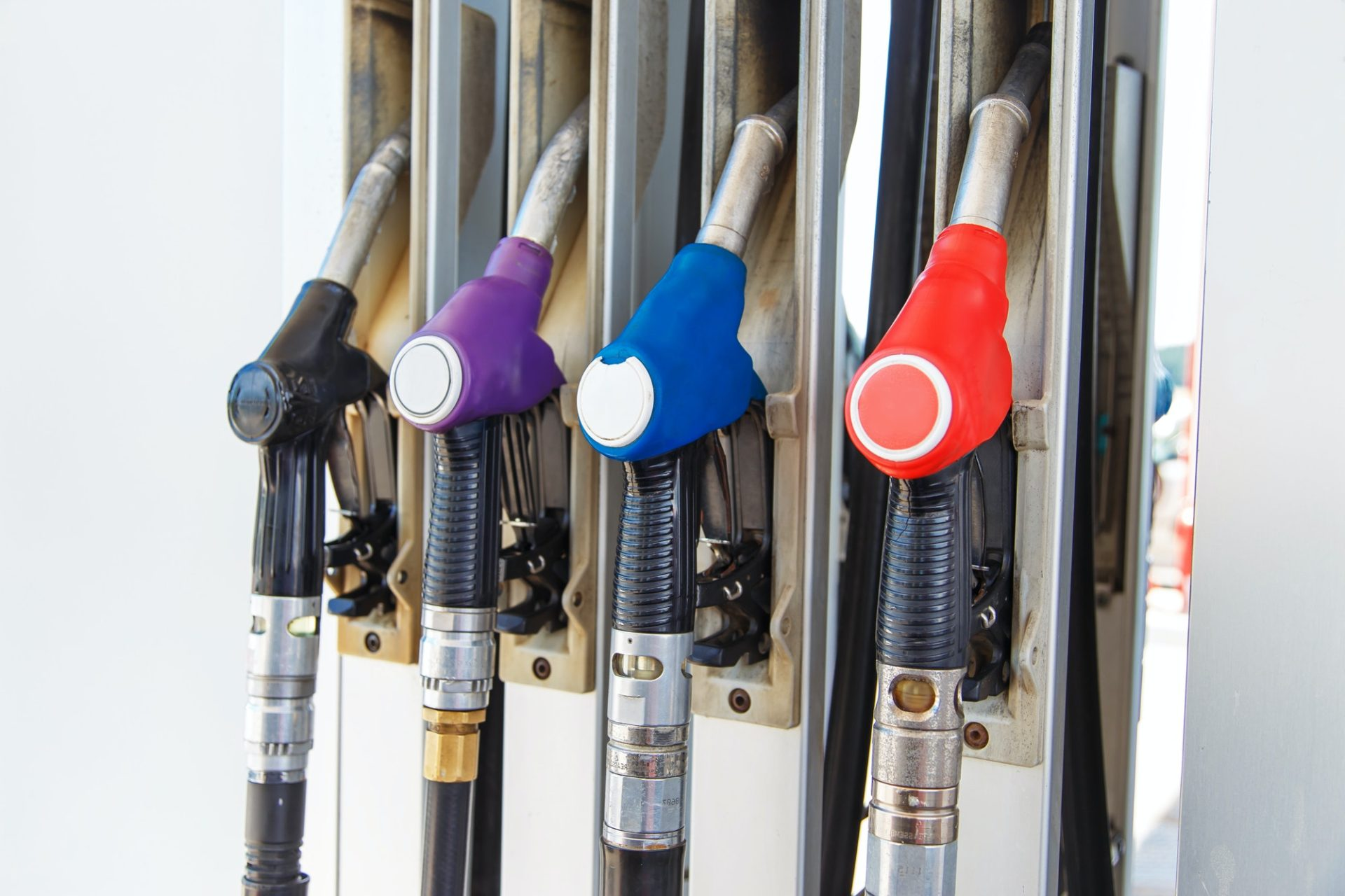 Fuel nozzle dispensing pump at gas station. The fuel for transportation concept.